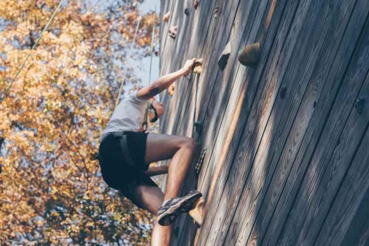 man wall climbing beside trees