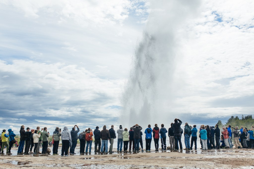 Crowds lined up side by side watching Geysir explode