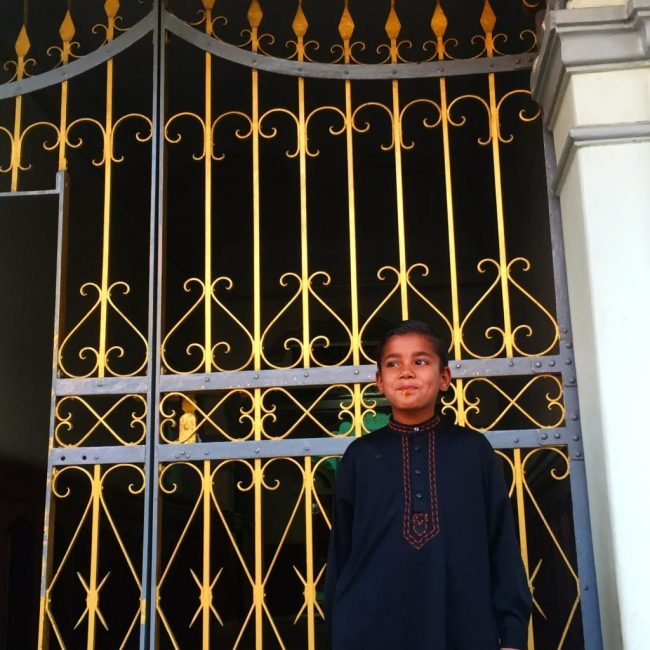 Young boy in black robe standing in front of gold gate of a mosque