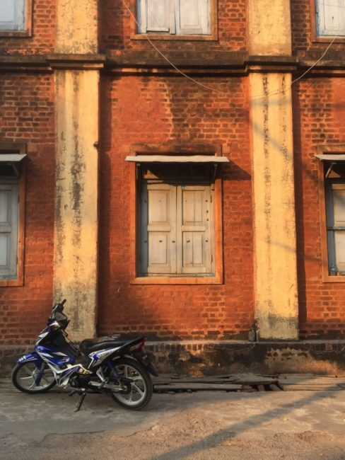 Motorbike parked in front of a brick building
