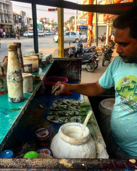 Man making betel nut packets from a street cart