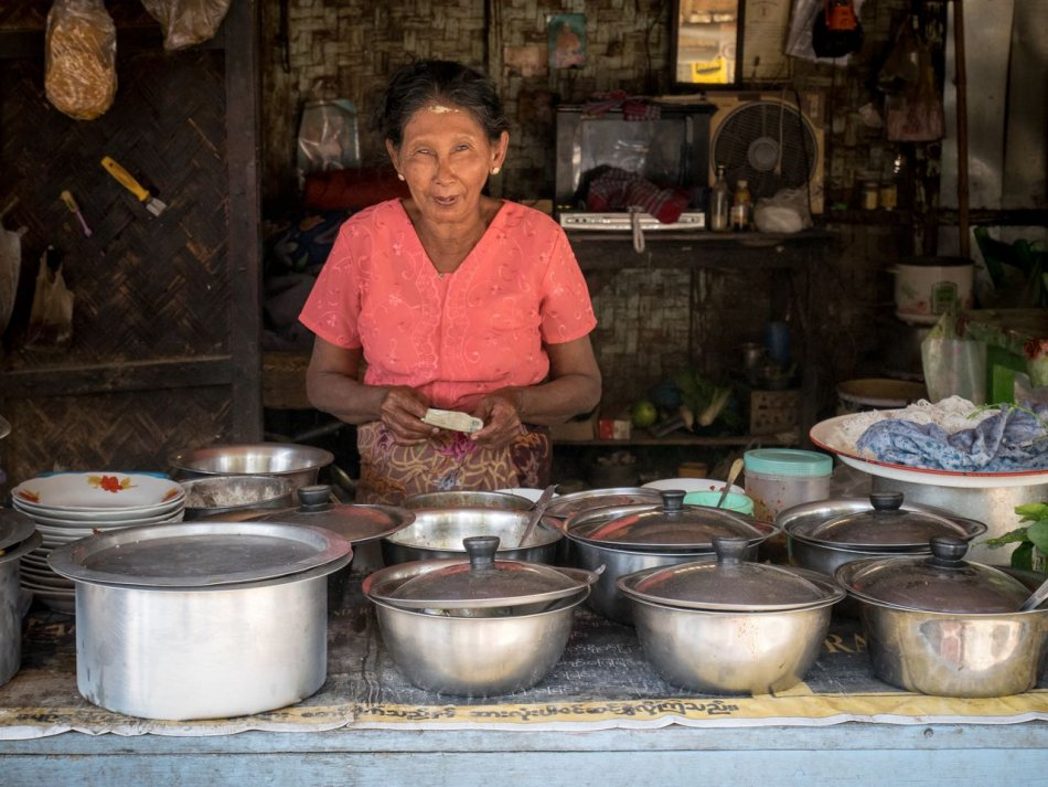 Woman standing over numerous silver pots of food