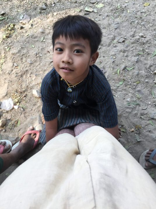 Young child looking up at me with his hands wrapped around my legs