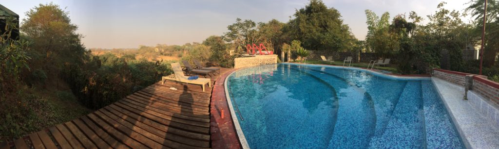 Panoramic photo of the in-ground pool surrounded by green trees and a view of Yenangyaung in the background