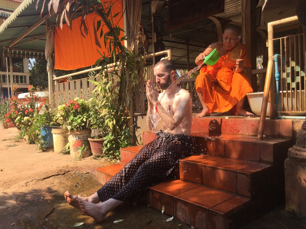 Me sitting on the steps of Wat Po Bantey Chey while an orange robed monk pours water over my head