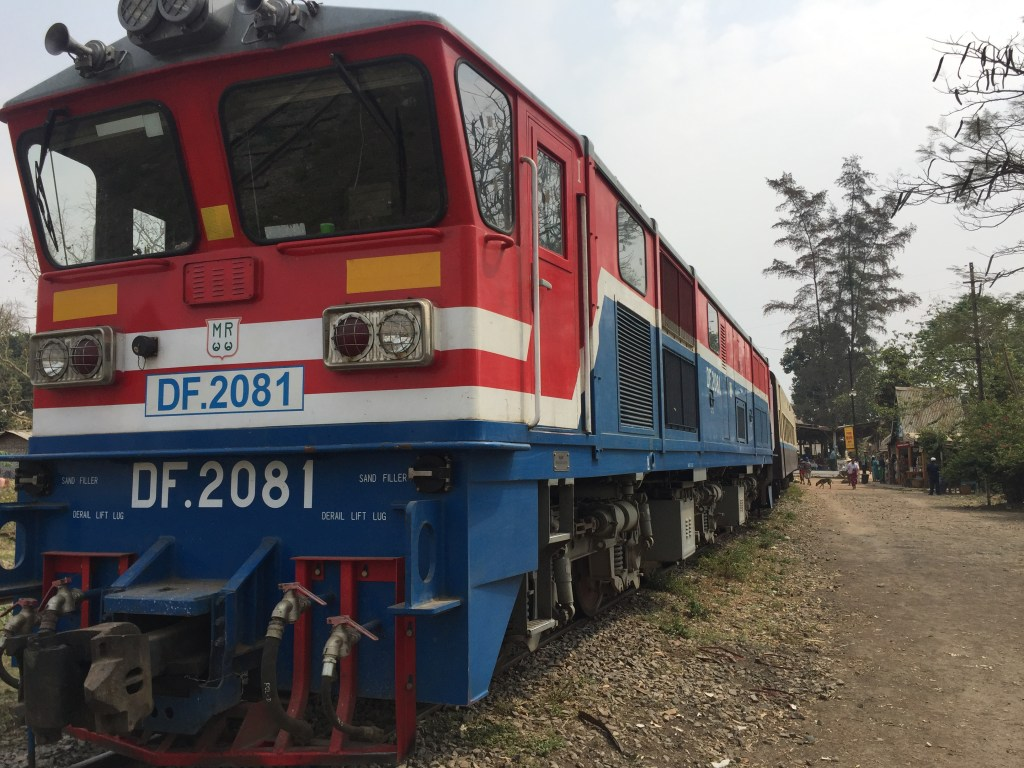 Photo of the red white and blue diesel engine at a stop in Shan State