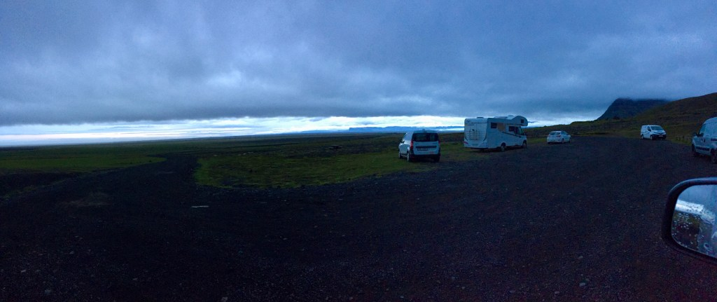 A few campers parked in a lot against a dramatic cloudy sky background