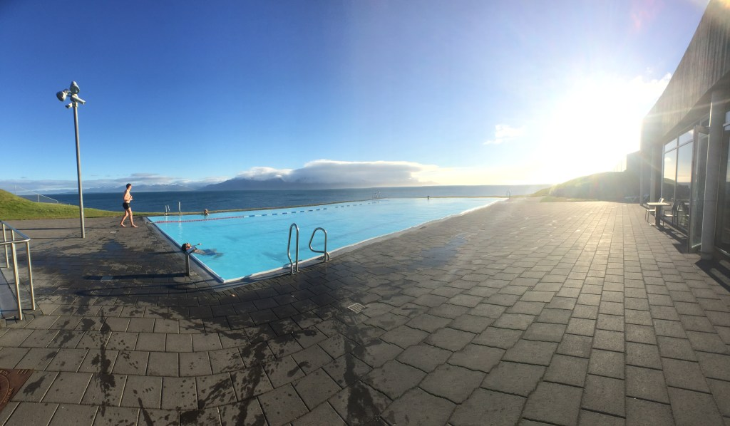 Panorama of the Hofsos swimming pool looking out onto a blue sky and deep blue water background of Skagafjordur and the Greenland Sea