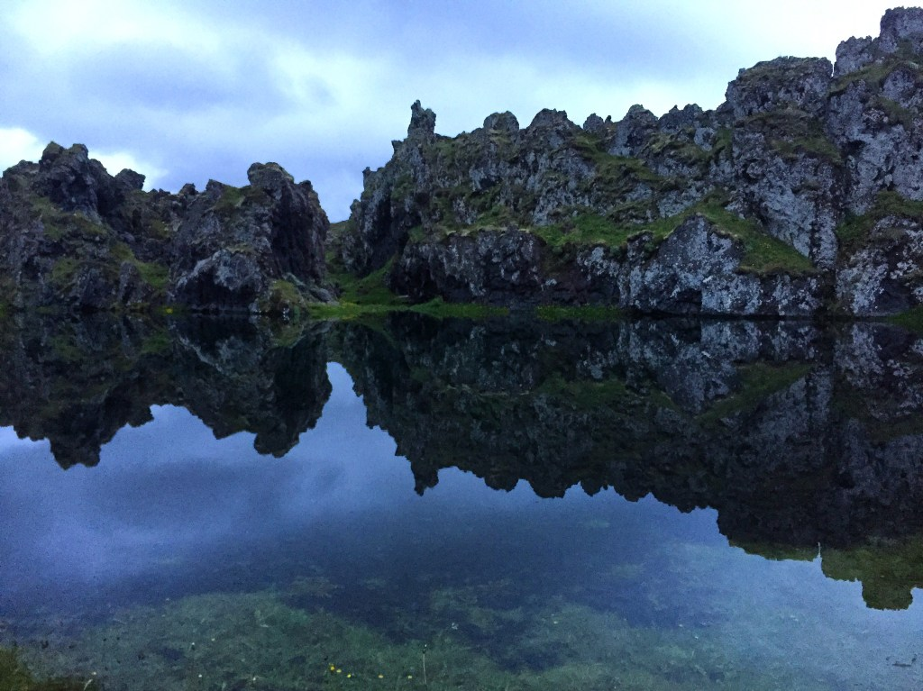 Mirror effect at Djupolon lagoon with rock formations reflected in the still water