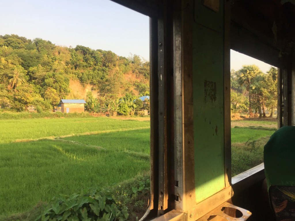 View out the train window, green fields, small farm and hills in the background