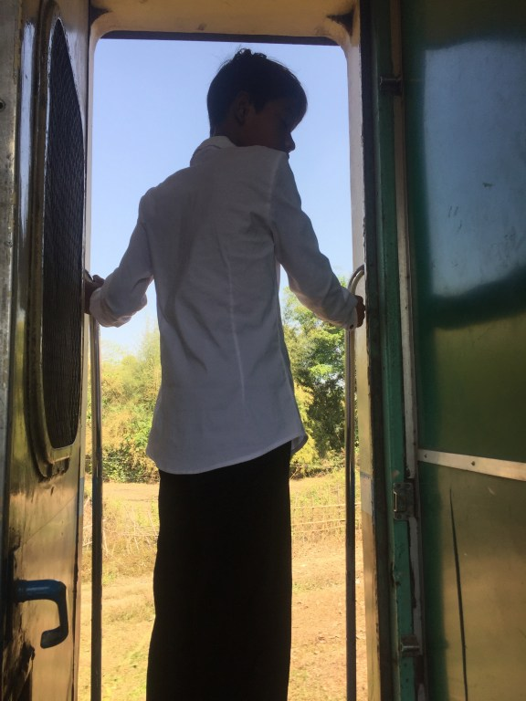 Young man stands in the doorway and looks out at the countryside on the train to Mawlamyine