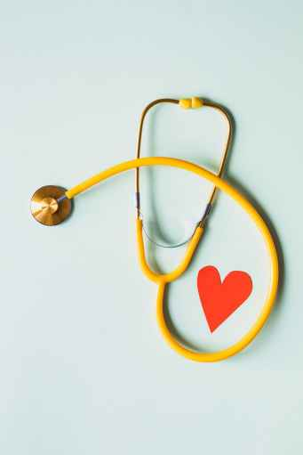 medical stethoscope with red paper heart on white surface