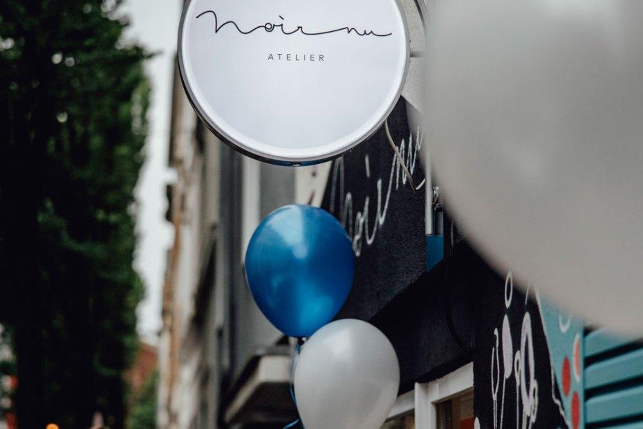 Außenansicht des Atelier Noir nu auf der Rothehausstraße zur Eröffnung mit Luftballons und Nadine Migesel.