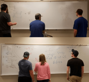 students at a whiteboard working on physics