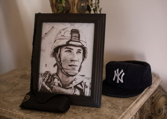 "A portrait of Lance Cpl. Gregory Buckley Jr. in his family's home in Oceanside, N.Y. He was shot to death in 2012 by a teenage ""tea boy"" living on his base in Helmand Province. Credit Kirsten Luce for The New York Times"