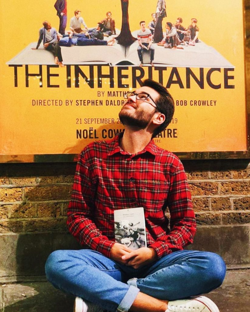 Austin in London under a poster for The Inheritance show.