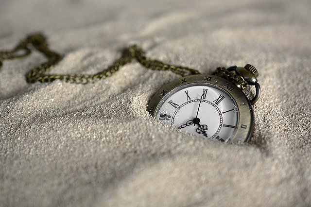 "This is a picture of a watch on a chain stuck in the sand to represent ""such a time as this."""