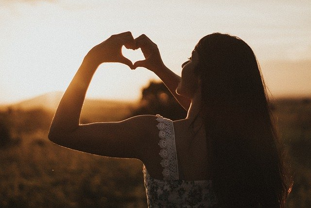 A girl faces the setting sun with her fingers shaped like a heart to represent making melody in your heart.