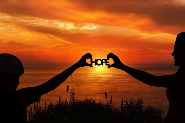 """This is a sunset with 2 people holding a sign that says """"hope."""" It represents encouragement for the suffering Christian."""