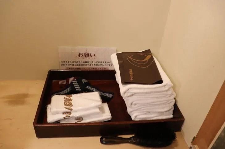 ニューフジヤホテルの部屋のクローゼットの中に置かれたタオルと浴衣の紐