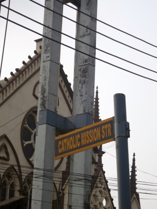 named for the mission buildings on either side of the street which included Holy Cross Catholic Church