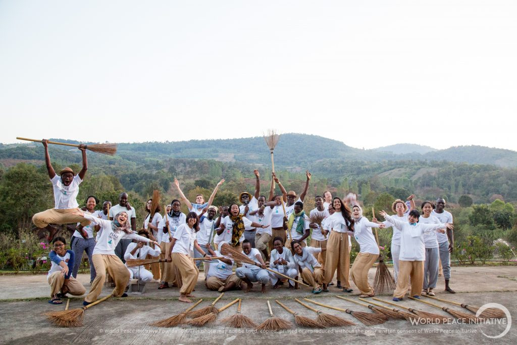 Group photo of the Amani Africa Fellows full of joy and peace, making silly poses and jumps with broomsticks