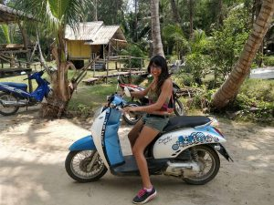 Narissa on a blue and white scooter in Ko Phangan, Thailand