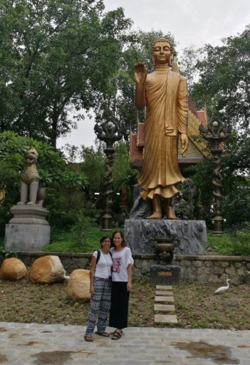 Two ladies standing under a golden Buddha statue wearing tops with sleeves and baggy trousers