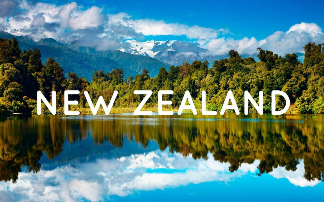 "View of the New Zealand landscape, trees on the distant edge of a lake with the Southern Alps in the background. White letters spelling ""New Zealand"" across the centre of the image."