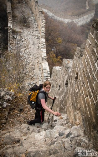 A hiker looking up from the crumbling Great Wall of China.