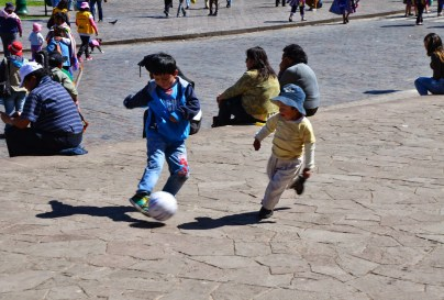 Children playing football in Plaza de Armas in Cusco, Peru