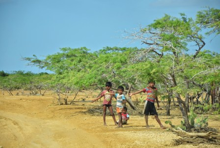 Wayúu children holding a rope across the road in La Guajira, Colombia