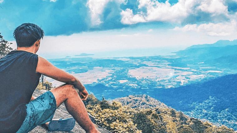 崖の上に座っている男性