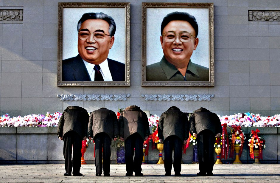 North Koreans bow beneath portraits of the late leaders Kim Jong