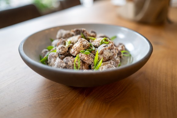Sous Vide Chicken Gizzard with green scallions in a white bowl