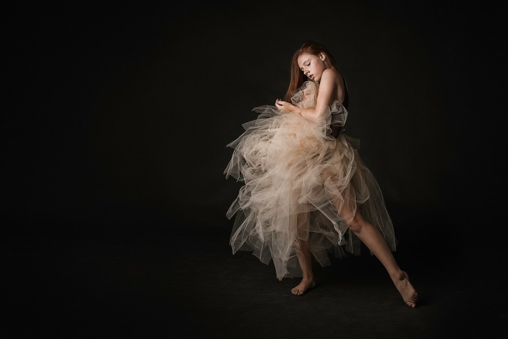 Mary Crum redhead studio photo portrait with long cream fluffy tulle skirt