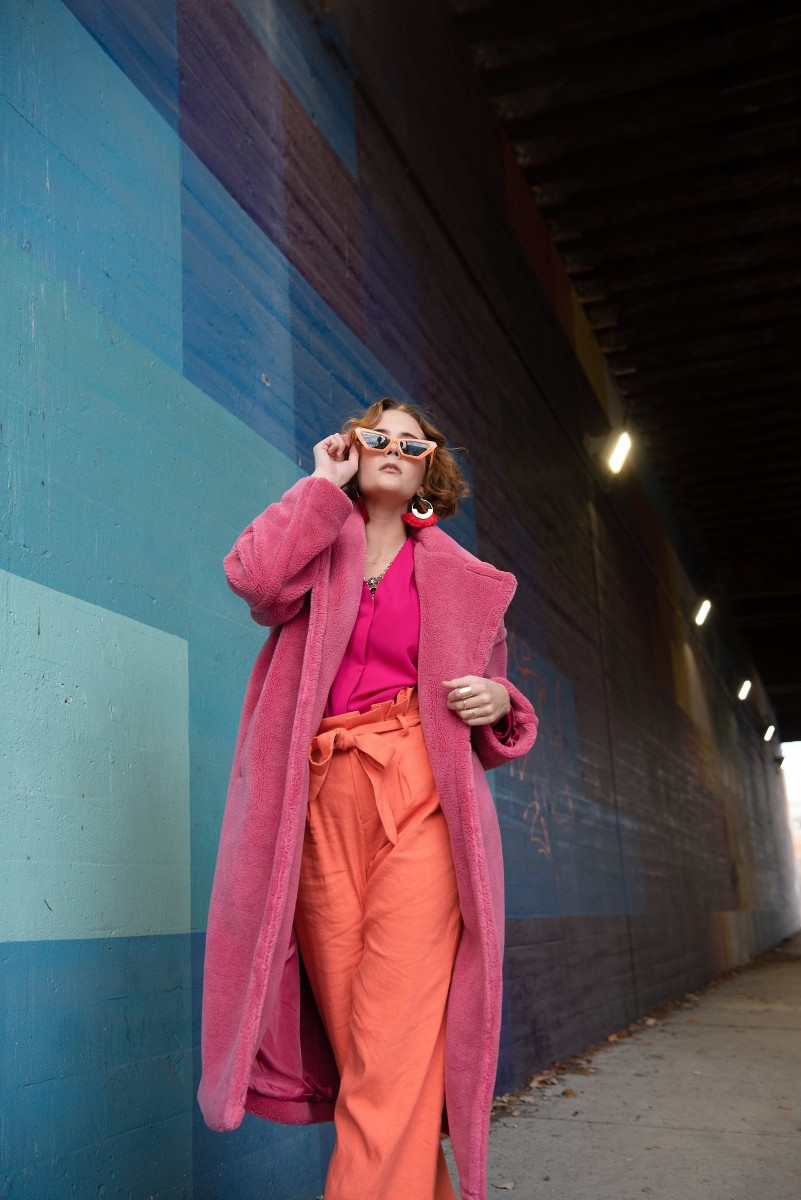 Madelyn Jackson Pink fur coat bold outfit with Blue background