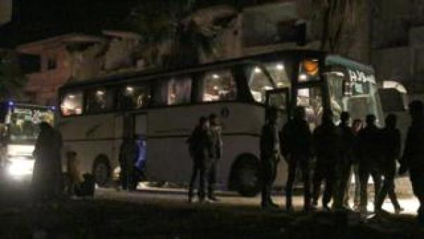 People prepare to board a bus to evacuate one of the few remaining rebel-held pockets in Arbin, Syria warfare