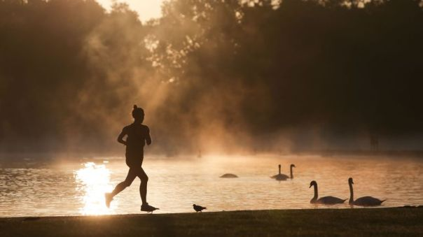 A jogger runs past the Round Pond as the sun rises at Kensington Gardens in London on August 31, 2017