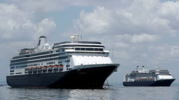 The Zaandam cruise ship, left, carrying some guests with flu-like symptoms, is anchored shortly after it arrived to the bay of Panama City