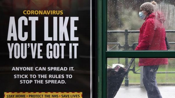 A person makes their way past an 'Act like you've got it' government coronavirus sign at a bus stop in Bournemouth, Dorset, during England's third national lockdown to curb the spread of coronavirus. Picture date: Tuesday February 16, 2021.