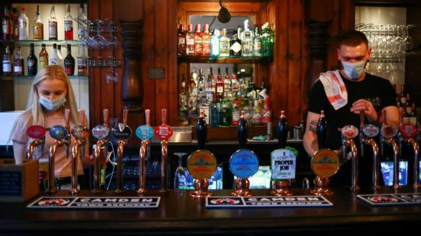 Bartenders pour drinks in a pub