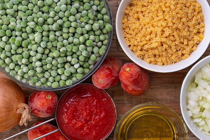 Ingredients for pasta piselli. Olive oil, onion, tomatoes, and green peas.