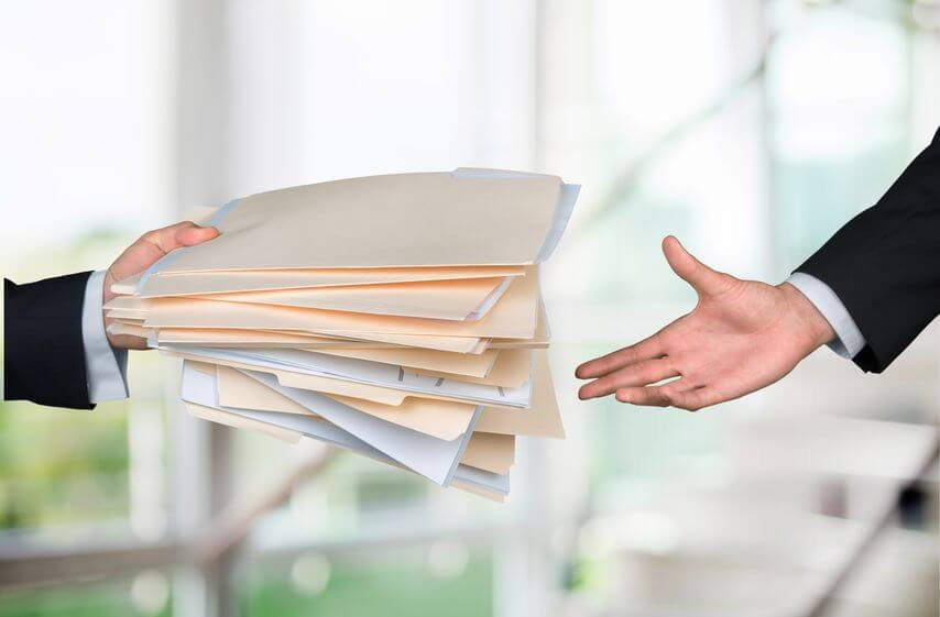 businessman handing stack of documents to another man