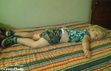 Toddler sprawled out on bed