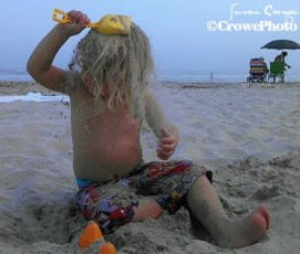 toddler putting sand in hair at beach