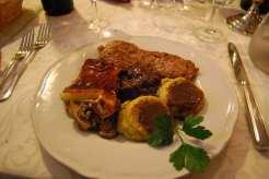 Piatto misto con funghi, polenta, carne di cervo, salsiccia e formaggio Puzzone - non è una battuta - alla brace.