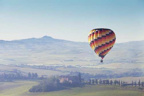 big balloon flies over rural houses, Tuscany, Italy