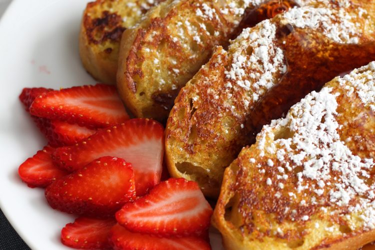 plated vegan french toast with powdered sugar and strawberries on a plate