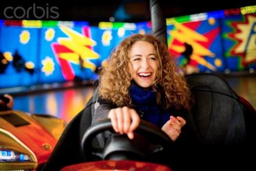 Teenage girl driving bumper car in amusement park
